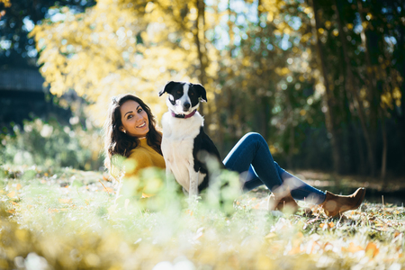 Happy relaxed woman with her dog in autumn.