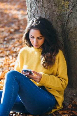Casual young woman using her cell phone and sitting outdoor in autumn.