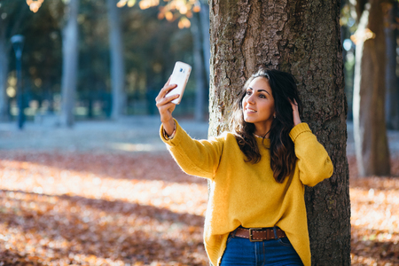 Casual beautiful young woman posing for smartphone selfie photo and touching her hair at city park in autumn.