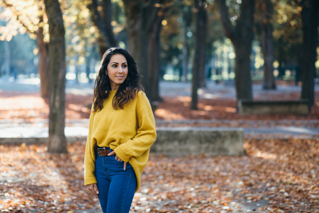 Cheerful casual woman walking at city park in autumn. Fall season fashion.