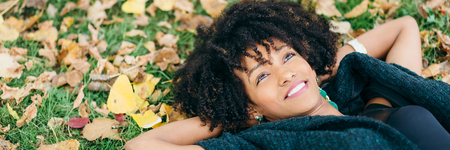Autumn tranquility and relax. Banner of afro hair style happy woman relaxing and smiling.