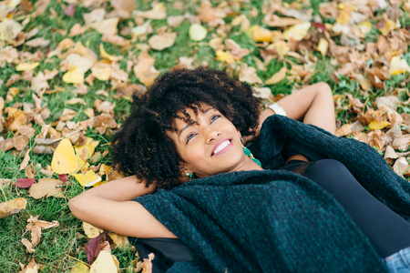 Young black successful woman with afro hair style relaxing in autumn. Happiness and relax concept.