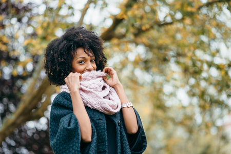 Black stylish woman wearing warm scarf in  autumn cold day.