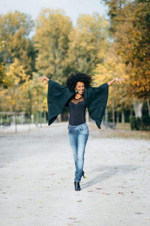Young happy stylish woman having fun and dancing in autumn at city park. Black afro hair style female model. 스톡 콘텐츠