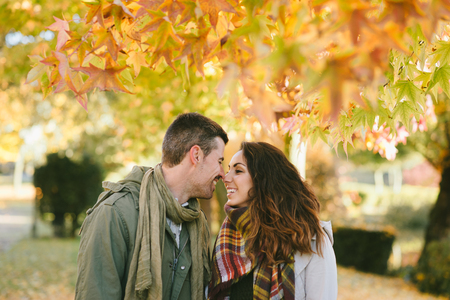 Caring young couple about to kiss under autumn tree at the park. Romantic man and woman in love.