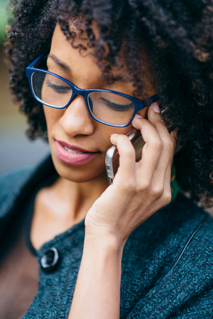 Close up of young black woman talking on the phone and wearing eye glasses. Stock Photo