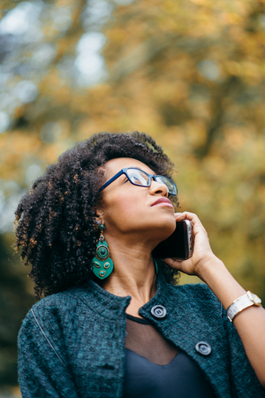 Young black woman talking on cell phone outside at the park in autumn season. Fashionable girl with afro hair style. Stock Photo