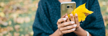 Detail of woman using her phone and holding autumn yellow leaves. Fall season mobile communication banner. Stock Photo