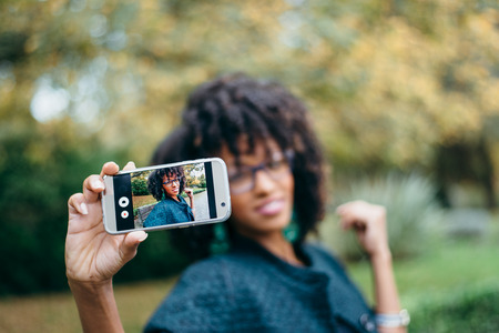 Fashionable black woman taking selfie photo with smartphone in autumn at the park. Afro stylie hair.