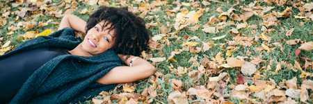 Autumn tranquility and relax. Banner of afro hair style happy woman lying down on the ground and smiling. Stock Photo