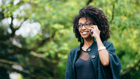 Young expressive black woman receiving surprising news on cell phone outside at the park in autumn season. Fashionable girl with afro hair.