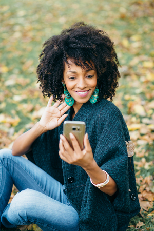 Young black woman taking selfie with smartphone for showing her earrrings. Autumn fashion and afro hair style. Stock Photo