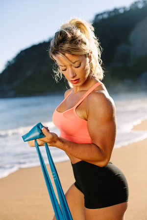 Fit strong woman training arms biceps with resistance band. Fitness summer morning workout at the beach.