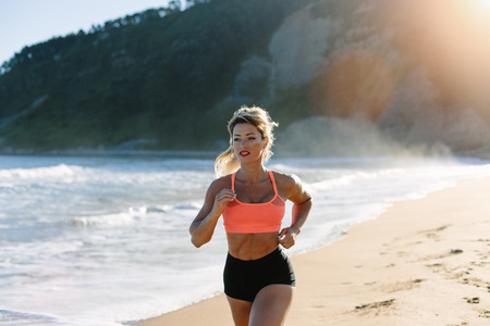 Blonde fitness woman running at the beach in summer morning.