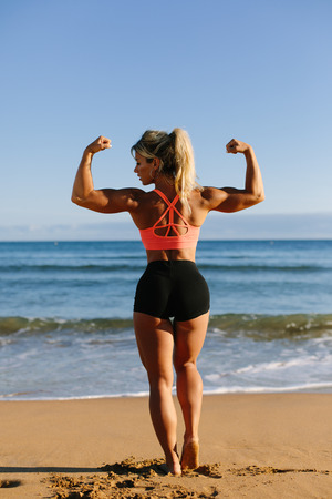Back view of strong fitness woman showing her arms biceps at the bech. Stock Photo