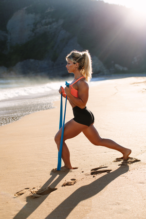 Fit woman training with resistance bands towards the sea. Fitness summer morning workout at the beach. Stock Photo