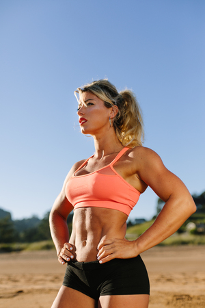 Strong motivated fitness woman during beach summer workout.