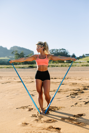 Fit woman training shoulders with resistance band. Fitness summer morning workout at the beach. Lateral raise exercise. Stock Photo