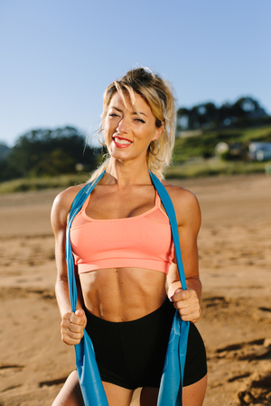 Fit cheerful woman posing at the beach with resistance band. Fitness summer morning workout.