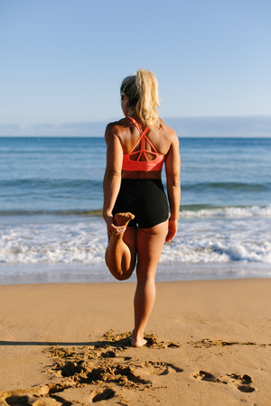 Fit woman doing leg stretching exercise towards the sea. Fitness summer morning workout at the beach. Stock Photo