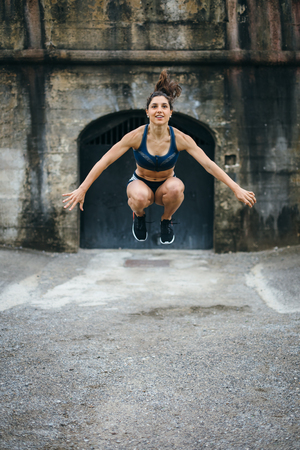 Sporty young female athlete doing high tuck jumps for explosive leg power.