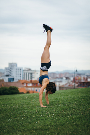 Fit woman doing a handstand at city park. Fitness outdoor workout and healthy lifestyle concept. Stock Photo