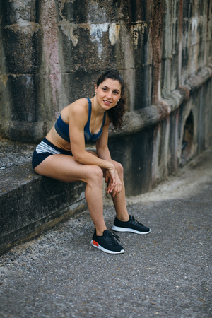 Cheerful female fit runner taking a rest during running urban workout.