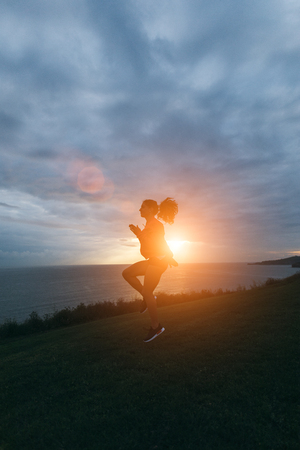 Sporty woman doing skipping warm up exercise for running outdoor at sunrise. Healthy lifestyle and sport concept.