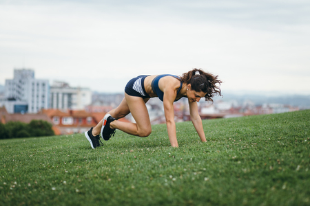 Sporty young female athlete doing burpees at city park for leg power workout. Stock Photo