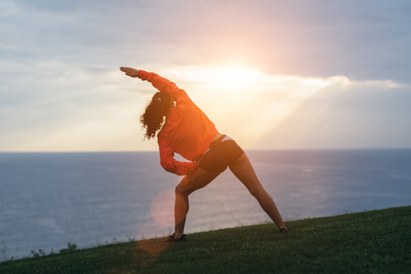 Sporty woman stretching and exercising outdoor at sunrise. Healthy lifestyle and sport concept. Stock Photo