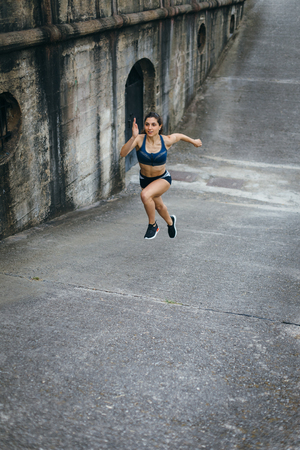 Sporty young female athlete running on a ramp for leg power training.