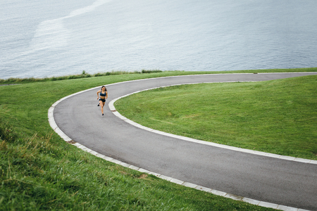 Sporty young female athlete running on a ramp near the sea for leg power training.