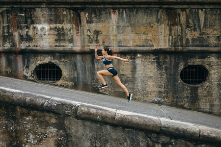 Sporty young female athlete running on a ramp for leg power training. Archivio Fotografico - 109803056
