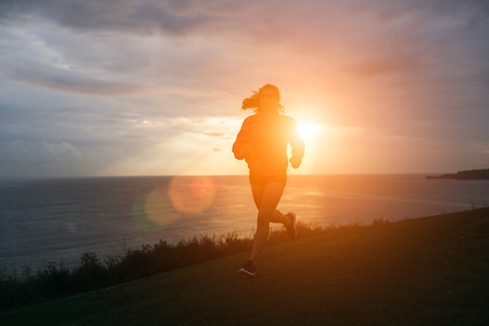 Sporty woman running outdoor at sunrise. Healthy lifestyle and sport concept.