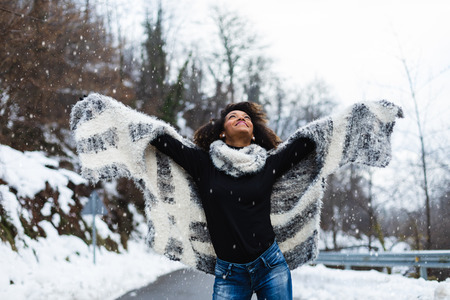 Blissful black woman raising arms under the snow in winter at mountain road. 스톡 콘텐츠