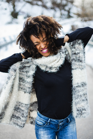 Young expressive black woman having fun in winter outdoor.