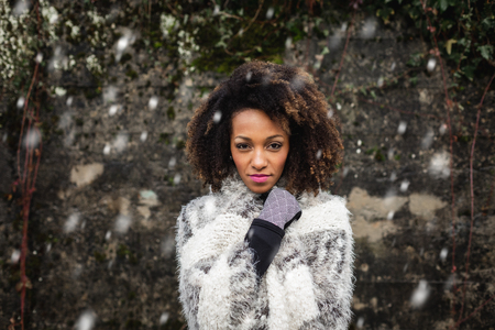 Stylish afro hair woman winter portrait under the snow. Female wearing warm clothes and gloves.