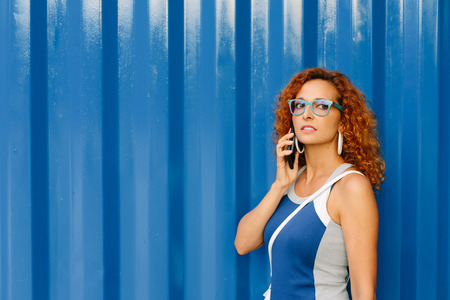 Young casual female entrepreneur on business cellphone call against blue metallic background. Modern woman lifestyle concept.