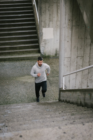Urban athlete running upstairs. Sporty man working out outside and climbing stairs in winter. Imagens