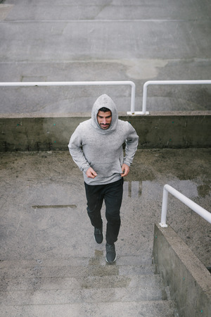 Urban athlete running upstairs under the rain. Banner of sporty man working out outside and climbing stairs in cold winter. Archivio Fotografico
