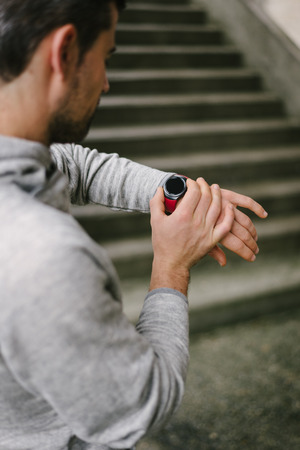 Modern sport and running technology concept.  Urban runner using sporty smart watch for training.
