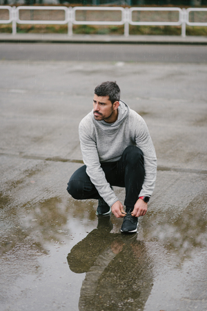 Sporty man getting ready for winter urban running and outdoor fitness workout under the rain . Sportsman lacing sport shoes on wet asphalt. Banque d'images - 116131999