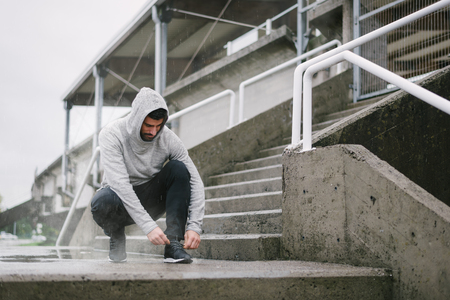 Sporty man getting ready for winter running and outdoor fitness workout under the rain. Sportsman lacing sport shoes on urban stairs. Banque d'images - 116132018