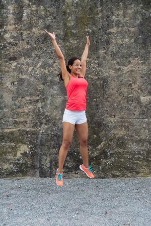 Fit happy woman jumping for celebrating fitness success.
