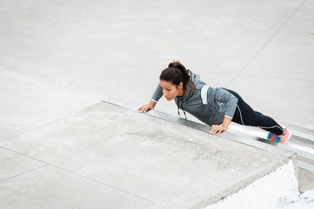 Strong woman doing push ups on urban stairs. Motivated female latin athlete training strength outside. Stock Photo