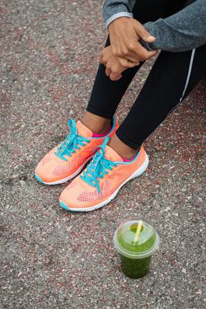 Detail of  running footwear and green detox smoothie. Fitness lifestyle and healthy nutrition concept.