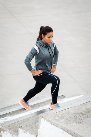 Leg lunges exercise on stairs. Fitness woman working out in the city. Stock Photo