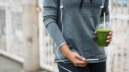 Detail of woman holding green detox smoothie and smartphone while taking a workout rest. Urban fitness lifestyle and healthy nutrition concept.