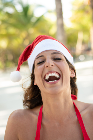 Woman laughing and having fun at tropical beach during Christmas vacation. Happy girl wearing Santa Claus hat.