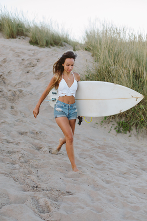 Joyful young surfer running to the water for surfing. Stock Photo